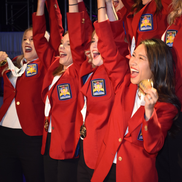 Students with hands raised in excitement and holding winning medal